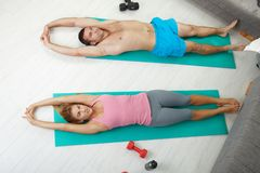 Fittness at home. Young couple doing exercises lying on fitness mattress in living room. Overhead shot Royalty Free Stock Images