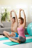 Fittness at home. Young couple sitting at fitness mattress and streching before exercises Royalty Free Stock Photos