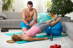 Fittness at home. Young couple doing abdominal exercise with fit ball in living room, smiling Royalty Free Stock Photography