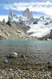 Mount Fitz Roy rising above clear blue glacial lake, Argentina. Hiking up to mount fitz roy and being rewarded with blue sky and clear blue glacier lake royalty free stock photo