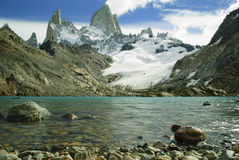 Fitz roy peaks with clear blue glacial lake from low perspective. Hiking up to mount fitz roy and being rewarded with blue sky and clear blue glacier lake royalty free stock image