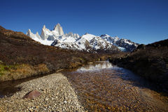 Fitz Roy and a River. Fitz Roy on a clear winter morning. Landscape has many dead bushes and trees. Foreground is a river with a rocky shoreline and perfectly Stock Photography