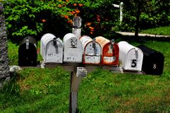 Fitzwilliam, NH: USPS Rural Mailboxes. FITZWILLIAM, NEW HAMPSHIRE:  A row of rural USPS metal mail boxes mounted on a wooden shelf Stock Image