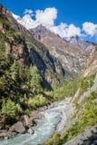 Fiume che viene attraverso la valle fra le grandi montagne Fotografia Stock Libera da Diritti