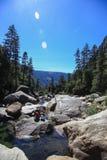 Fiume con l'uomo di pesca in foresta in parco nazionale di Yosemite Fotografia Stock