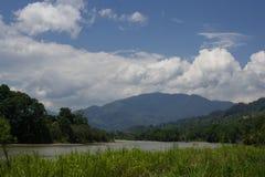 Fiume con le montagne e le nuvole nel fondo Immagini Stock Libere da Diritti