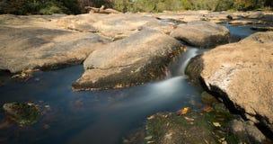 Fiume con le rocce e le piccole cascate Immagini Stock Libere da Diritti