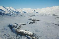 Fiume congelato attraverso una valle della montagna Fotografie Stock Libere da Diritti