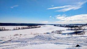 Fiume congelato nell'inverno coperto di neve Bello paesaggio del lago in ghiaccio Chiaro cielo blu con le nuvole Fotografie Stock