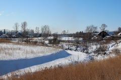 Fiume congelato paesaggio rurale di inverno un villaggio sul pendio della riva un chiaro giorno immagine stock libera da diritti