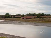 Fiume del lago attraverso la campagna con agricoltura del tetto della casa dell'azienda agricola Immagine Stock