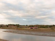 Fiume del lago attraverso la campagna con agricoltura del tetto della casa dell'azienda agricola Fotografia Stock Libera da Diritti