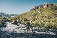 Fiume dell'incrocio dell'uomo del viaggiatore all'avventura di concetto di stile di vita di viaggio di spedizione delle montagne Immagini Stock