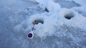 Fiume della canna da pesca nell'inverno su ghiaccio vicino al foro archivi video
