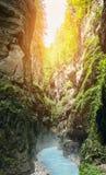 Fiume della montagna con chiara acqua blu sui precedenti delle rocce e della luce solare fotografia stock