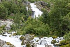 Fiume della montagna da ghiaccio fuso del ghiacciaio di Briksdalsbreen ad estate Fotografie Stock