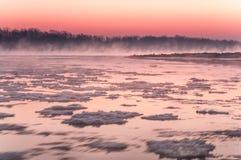 Fiume di congelamento coperto in nebbia durante il crepuscolo Fotografia Stock