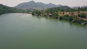 Fiume e diga di vista aerea sulle colline verdi e sulle montagne del fondo Fuco di volo sopra il fiume con la diga ed il litorale stock footage