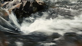 Fiume a flusso rapido che si schianta sopra il fondo delle rocce stock footage