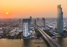 Fiume nella città di Bangkok con la costruzione dell'alta carica al tramonto Immagine Stock