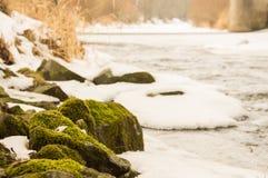 Fiume parzialmente congelato con la riva pietrosa Fotografia Stock Libera da Diritti