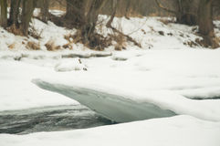 Fiume parzialmente congelato con un pezzo di ghiaccio di sporgenza Immagini Stock Libere da Diritti
