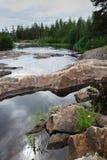 Fiume rapido con le rive del fiume pietrose nella foresta di taiga Immagini Stock