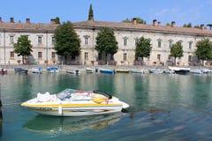 Fiume (river) Mincio, Peschiera Del Garda Italy. Looking across the river (Fiume Mincio) in Peschiera Del Garda in Italy.  There is a small boat moored in the Stock Photos