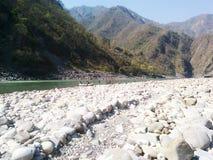 Fiume, rocce della riva del fiume e montagne fotografia stock libera da diritti