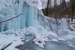 Fiume selvaggio, belle cascate congelate e neve fresca in una foresta della montagna, un giorno di inverno freddo Immagini Stock Libere da Diritti