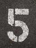 Five. A close up on white stenciled number five on black pavement Royalty Free Stock Image