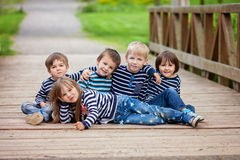 Five adorable kids, dressed in striped shirts, sitting on a brid Stock Image
