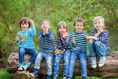 Five adorable kids, dressed in striped shirts, sitting on wooden Royalty Free Stock Photos