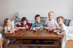 Five adorable kids, eating spaghetti at home Stock Photos
