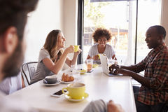 Five adult friends sitting in a cafe, over shoulder view royalty free stock photography