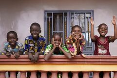 Free Five African Children Greeting Bypassers From A Colonial House Balcony Stock Photography - 172697882
