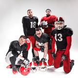 The five american football players posing with ball on white background Stock Photo