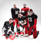 The five american football players posing with ball on white background Royalty Free Stock Photography