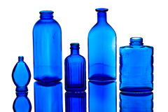 Five Antique Blue Bottles. Five Antique Bottles on mirror surface Royalty Free Stock Photos