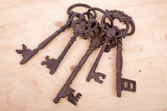 Five antique rusty keys. On a wooden background Royalty Free Stock Photo