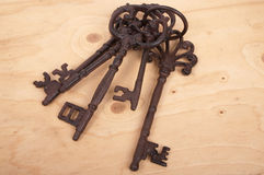 Five antique rusty keys on wooden background Stock Photo