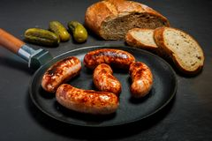 Five appetizing ruddy juicy sausages fried in large frying pan. Served with sliced rye bread and three pickled cucumbers on black background royalty free stock photos