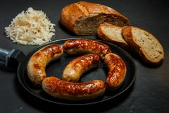 Five appetizing ruddy juicy sausages fried in large pan. Served with sliced rye bread and sauerkraut on black background royalty free stock photos