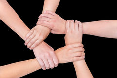 Five arms of children holding together on black background Stock Photos