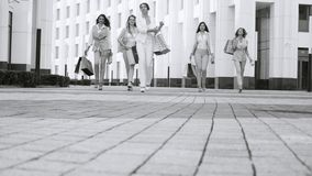 Five attractive business women walking in the city. Five attractive business women with shopping bags walking near business centre. Summer day. Black and white stock video footage