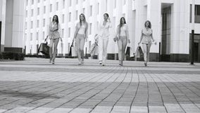 Five attractive business women walking in the city. Five attractive business women with shopping bags walking near business centre. Summer day. Black and white stock footage