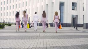 Five attractive business women walking in the city. Rear view. Five attractive business women with shopping bags walking near business centre. Summer day. Color stock video