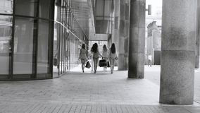 Five attractive business women walking in the city. Rear view. Five attractive business women with shopping bags walking near business centre. Summer day. Black stock video