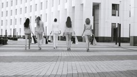 Five attractive business women walking in the city. Rear view. Five attractive business women with shopping bags walking near business centre. Summer day. Black stock video footage