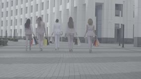 Five attractive business women walking in the city. Rear view. Five attractive business women with shopping bags walking near business centre. Summer day. No stock footage
